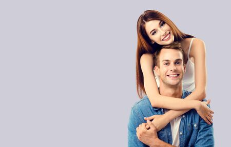Love, relationship, dating, flirting, lovers, romantic concept - lovely couple, standing close to each other, over grey background. Copy space for some text.
