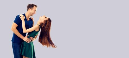 Love, relationship, dating, flirting, lovers, romantic concept - full body portrait of hugging or dancing couple, looking at each other. Over grey color background. 스톡 콘텐츠