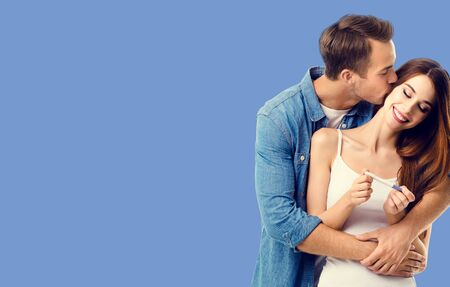 Love, relationship, happy lovers, family concept - amorous happy couple, finding out results of a pregnancy test. Blue color background.