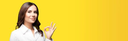 Portrait of smiling young brunette businesswoman, showing ok hand sign gesture, over orange yellow background. Success in business concept picture.