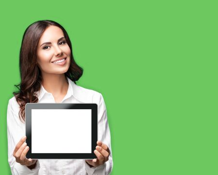 Cheerful beautiful brunette confident businesswoman showing blank no-name tablet pc monitor, over green color background, with copy space area for some text. Success in business concept.