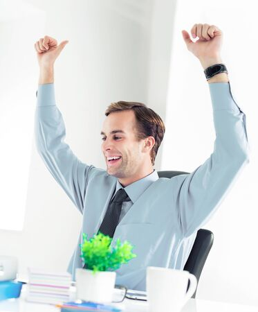 Very happy or surprised confident businessman in shirt and tie, punching the air, working at office. Success in business, job and education concept.