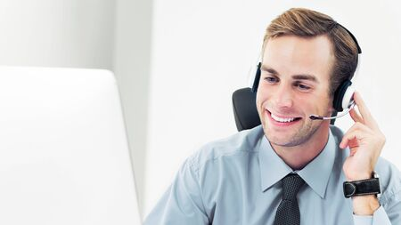 Portrait of happy smiling support phone male operator or sales agent in headset, confident shirt and tie, with computer. Help service and client consulting call center concept.