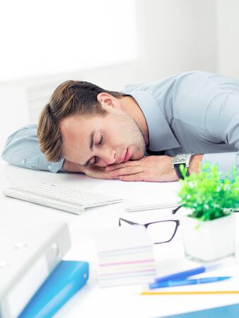 Very tired confident businessman in shirt, sleeping at workplace, at office. Business, job and overworking concept.