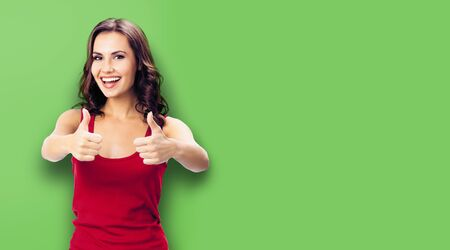 Young happy woman in casual clothing, showing thumbs up gesture, over green color wall background. Happy girl in red dress. Brunette model at studio picture.