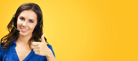 Call center service. Customer support phone sales operator showing thumb up hand sign like gesture, copy space for some text or slogan, on yellow orange background. Young attractive woman in headset.