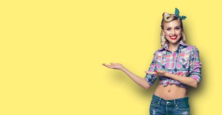 Happy smiling adorable woman showing. Excited girl in pin up style, showing something or copy space for advertise slogan or text. Retro fashion and vintage hairdo concept. Yellow background.