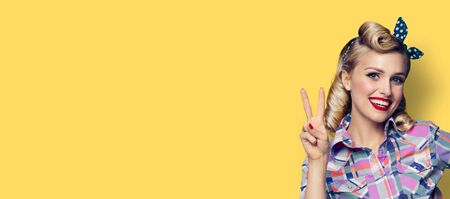 Pin up girl. Excited happy adorable woman showing two fingers or victory gesture hand sign. Retro fashion and vintage picture. Yellow background. Copy space for some slogan, imaginary or text.