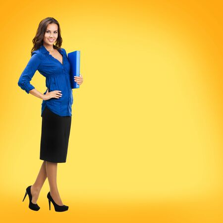 Full body portrait of attractive business woman with blue folder with copy space, isolated against yellow orange background. Brunette dark heared model at studio. Square composition.