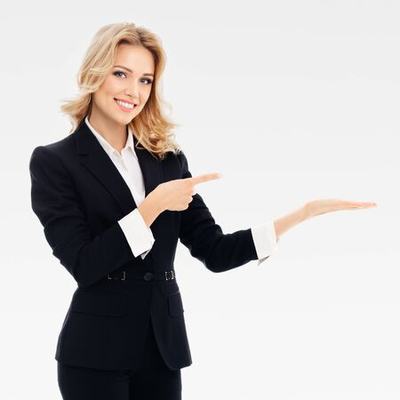 Smiling businesswoman, showing, holding or giving something or copy space for some slogan or text, over grey background. Caucasian blond model in business or sales advertision concept. Square composition.