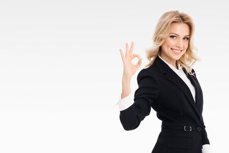 Happy smiling businesswoman showing okay gesture, on grey background, with blank copyspace area for slogan or text message. Caucasian blond model in business concept.