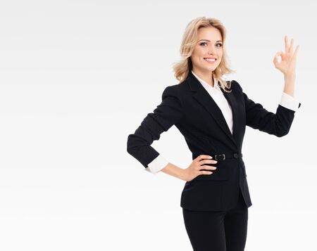 Happy confident businesswoman showing okay gesture, on grey background, with blank copyspace area for slogan or text message. Caucasian model in business presentation concept.