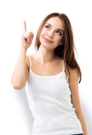 Souriante en levant une belle femme brune montrant quelque chose ou un espace de copie pour du texte ou un slogan, ou faisant un geste d'idée, isolé sur fond blanc.