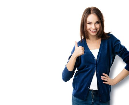 Portrait of brunette lovely woman in casual smart blue clothing, showing thumbs up gesture, isolated against white background. Emoshions and optimistic, positive concept.