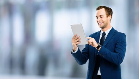 Portrait of smiling businessman using no-name tablet pc, standing against blurred office background. Success in business concept studio picture. Copy space for some text. Stock fotó