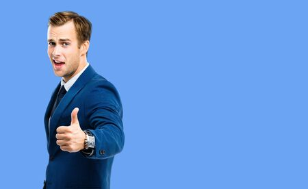 Excited young businessman showing thumbs up like hand sign gesture, in confident suit, over blue color background. Handsome happy man. Copy space for some slogan or advertising text. 스톡 콘텐츠