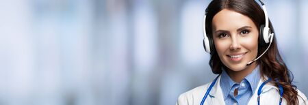 Medical call center servise. Online helping and consultation. Portrait of female doctor in headset, over blurred office background, with copy space empty place for some sign text or slogan.