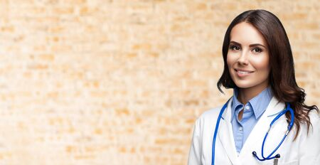 Portrait picture of happy smiling female doctor in white uniform coat and stethoscope, over loft style wall background. Healthcare, medical, medicine specialist - concept. Copy space.