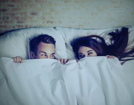 Young adult playful couple peeping from bedsheet on the bed at bedroom. Looking at each other. Love, relationship, dating, happy people, bedtime concept picture. Night light scene.