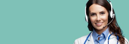 Medical call center servise. Online helping and consultation. Portrait of female doctor in headset, over green marine background, with copy space empty place for some sign text or slogan.