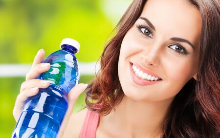 Portrait picture of happy woman with bottle of water