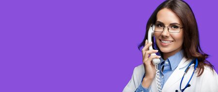 Portrait picture of happy smiling young doctor talking on phone, against purple violet background. Copy space for some sign, slogan or advertising text. Medical call center service. Stock Photo