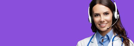 Medical call center servise. Online helping and consultation. Portrait of female doctor in headset, against purple violet background, with copy space empty place for some sign text or slogan. Stock Photo