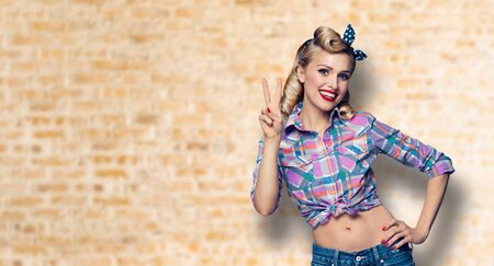 Pin up girl. Excited happy woman showing two fingers or victory gesture hand sign. Retro and vintage concept. Loft style wall background. Copy space for some advertise slogan, sign or text.