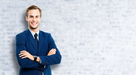Portrait of businessman in blue suit and tie, with crossed arms, standing against white brick wall background. Business success concept. Smiling man at studio picture. Copy space for some text.