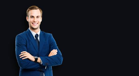 Portrait of businessman in blue suit and tie, with crossed arms, standing over black color background. Business success concept. Smiling man at studio picture. Copy space for some text. Stock fotó
