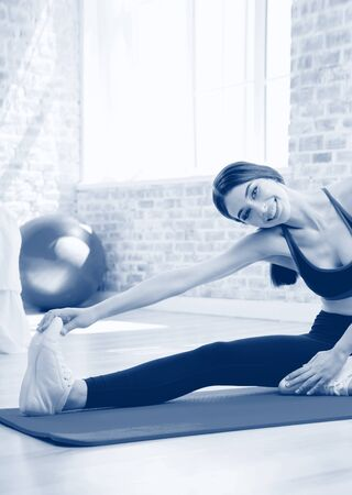 Beautiful happy smiling brunette girl on indoors workout. Stretching for calf and back of thigh muscle, warming down exercise. Healthy lifestyle, weight lossing and sporting. Black and white monochrome blue tone picture.