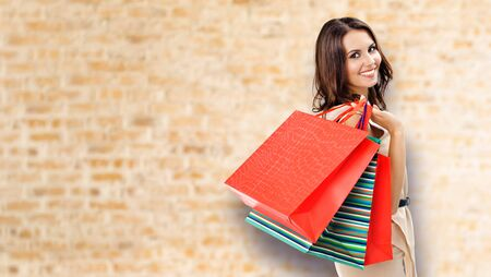 Shopping woman. Happy girl holding grocery bags, at loft style wall background. Copy space for some slogan, advertising or text. Brunette model - consumerism, sales and shopaholic concept picture. Banco de Imagens