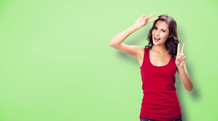 Happy excited woman in casual clothing, showing two fingers or victory gesture, over green color background. Happy girl in red dress. Brunette excited model at studio picture. Banco de Imagens