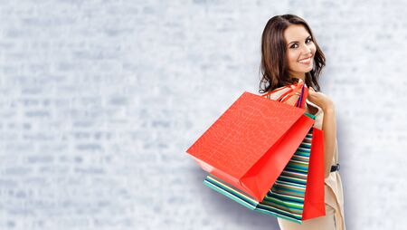 Shopping woman. Happy girl holding grocery bags, at white brick wall background. Copy space for some slogan, advertising or text. Brunette model - consumerism, sales and shopaholic concept picture. Banco de Imagens