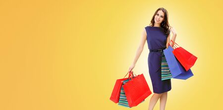 Portrait picture of happy woman with shopping bags, standing over orange yellow background, with copy space for some slogan, advertising or text message