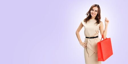 Portrait of happy smiling brunette woman holding red shopping bag, standing against light violet color background, with copy space for some slogan or text. Consumers and sales concept picture. Banco de Imagens