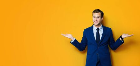Happy smiling businessman in blue confident suit, showing, holding or giving something or copy space for some slogan or text, over orange color background. Business concept. Standard-Bild