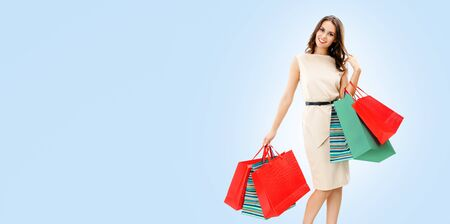 Portrait of happy smiling brunette woman holding red shopping bags, standing against light blue color background, with copy space for some slogan or text. Consumers and sales concept picture.