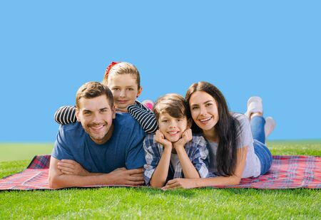 Portrait of smiling young parents and two children, lying together on a picnic blanket, outdoors. Love, family and happy childhood lifestyle concept. Blue sky background.