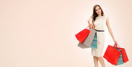 Portrait of happy smiling brunette woman holding red shopping bags, standing over light beige color background, with copy space for some slogan or text. Consumers and sales concept picture.