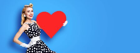 Very happy, excited woman holding red heart symbol, dressed in pin up, over blue color background. Love, sales or retro fashion concept. Wide horizontal banner composition picture with copy space. Banco de Imagens