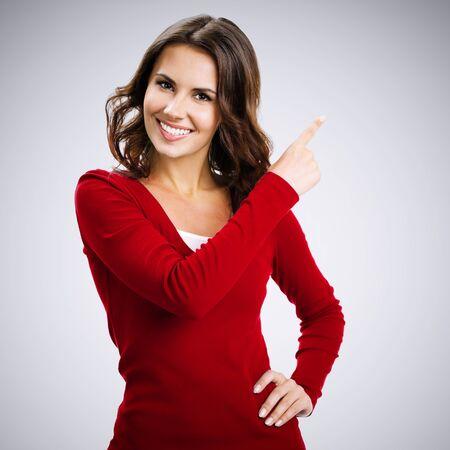 Studioporträt einer glücklichen brünetten Frau, die Kopienraum, visuelles Imaginäres oder etwas zeigt oder die virtuelle Taste auf grauem Hintergrund drückt