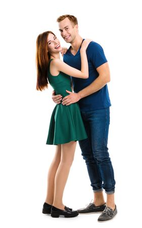 Smiling attractive young amorous couple. Full body length portrait image - embracing models at happy in love studio concept isolated over white background. Man and woman posing together. Youth fashion