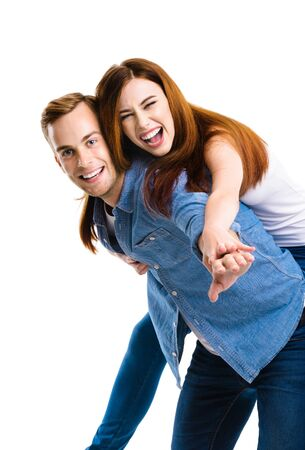 Smiling amorous funny young attractive couple. Portrait image of standing piggy back ride models in love studio concept, isolated over white background. Man and woman posing together.