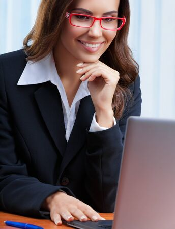 Portrait image of smiling businesswoman in black confident style suit and red eye glasses, working with laptop computer at office. Success in business, job and education concept shot.