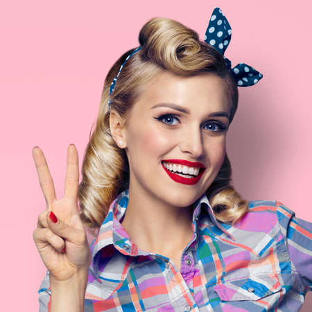 Portrait image - amazed pin up girl. Excited happy blond woman showing two fingers or victory gesture hand sign. Retro and vintage. Pastel pink color background. Square composition.