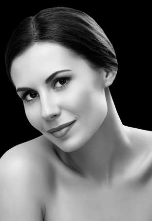 Portrait of beautiful young woman with naked shoulders. Black and white. Monochrome image.