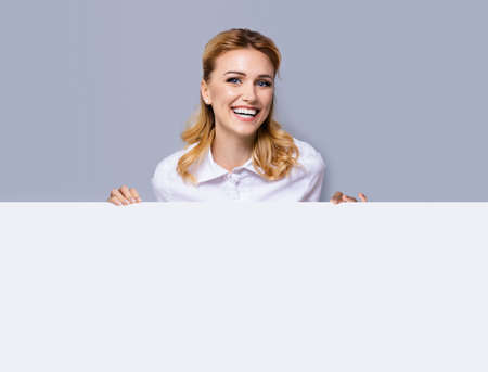 Very happy excited, laughing business woman in white confident clothing showing blank banner signboard. Success and advertising concept. Copy space empty place for some text or imaginary. Blond girl.