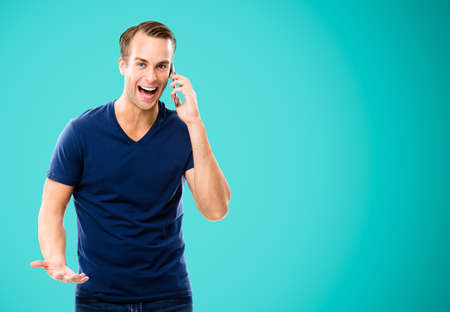 Good news! Very happy excited man in blue casual clothing talking on cell phone, isolated against aqua marine color background. Mobile, cell, emotions and success concept. Copy space for some text.