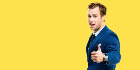 Excited happy businessman showing thumbs up like hand sign gesture, blue confident suit, on yellow color background. Handsome happy man. Copy space for some slogan or advertising text.
